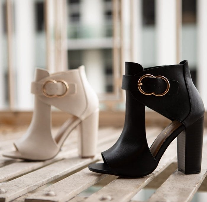 A cutout ankle bootie with a block heel, open toe and double buckle detail.