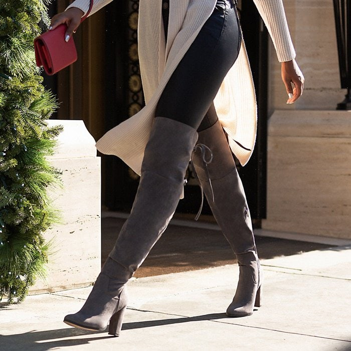 A thigh-high boot featuring a lace-up back with adjustable ties, block heel, and inner zipper closure