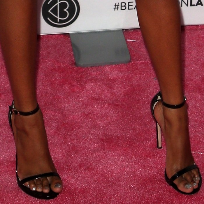 Skai Jackson's pretty feet and toes in black Nudist sandals