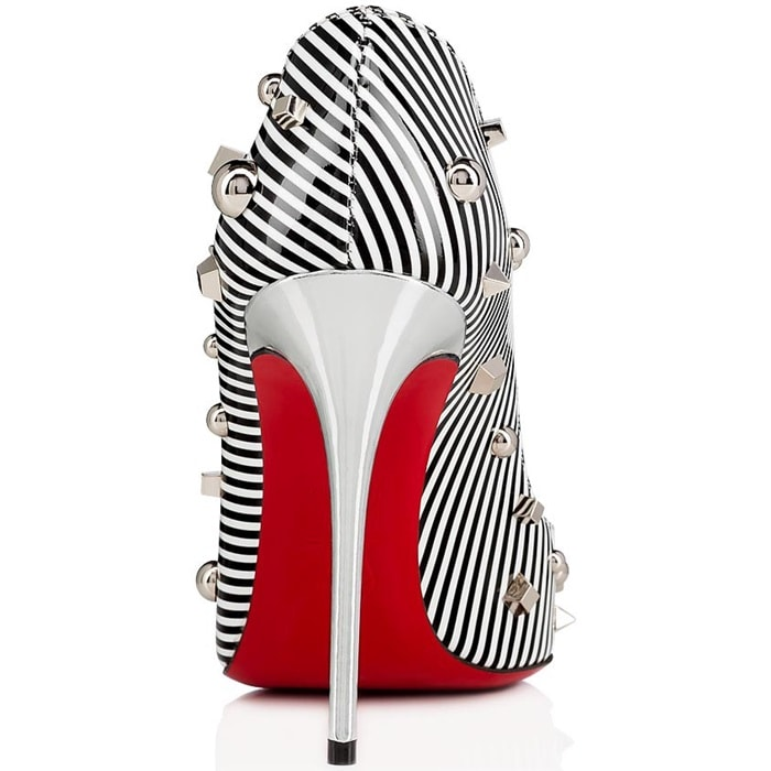 Mounted on a 100mm silver specchio stiletto heel, the pointed-toe model, covered in black and white striped patent leather and an array of studs, offers a subtly low-cut décolleté