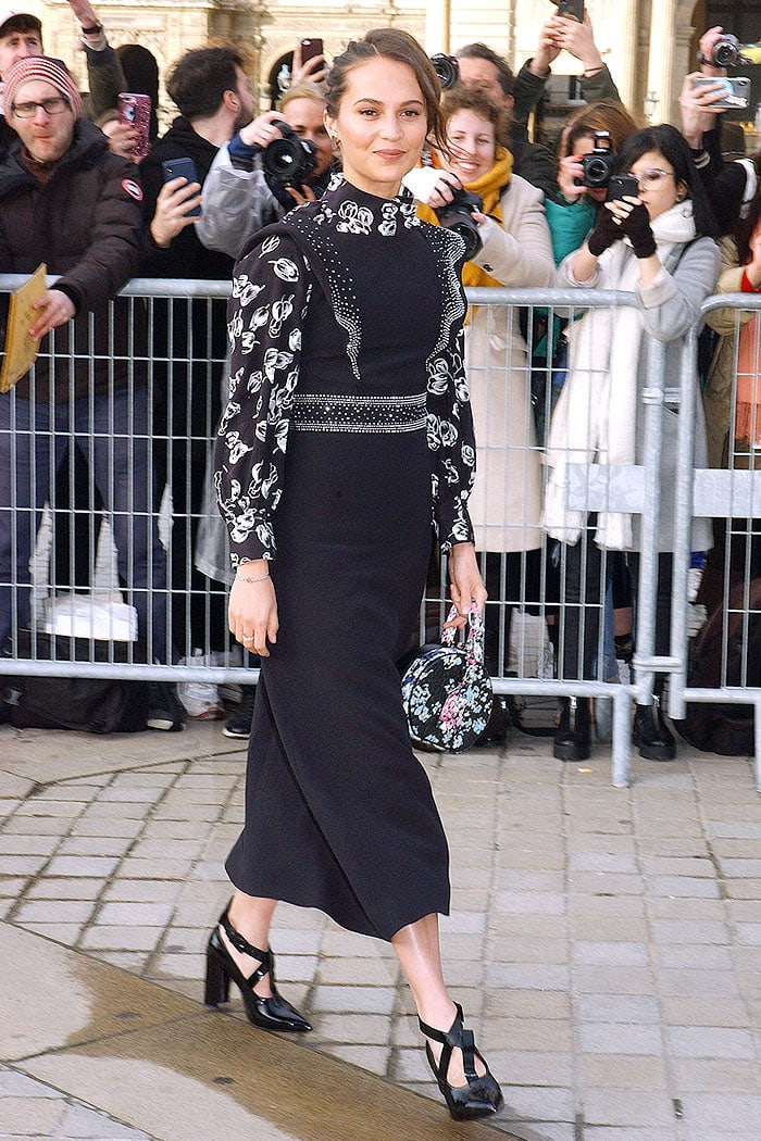 Alicia Vikander stepping out for the Louis Vuitton Fall 2019 fashion show in black-and-floral-print ensemble