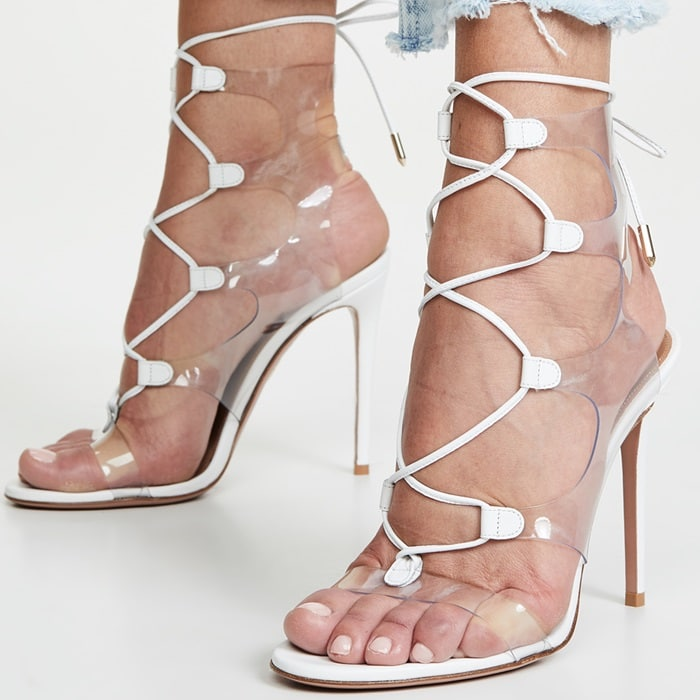 Crafted from sleek, on-trend PVC, style features a fresh white, slender heel and lacing that wraps and ties at the ankle