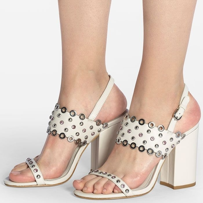 Crystals, studs and polished grommets shine up a quarter-strap sandal set on a super-chunky wrapped heel