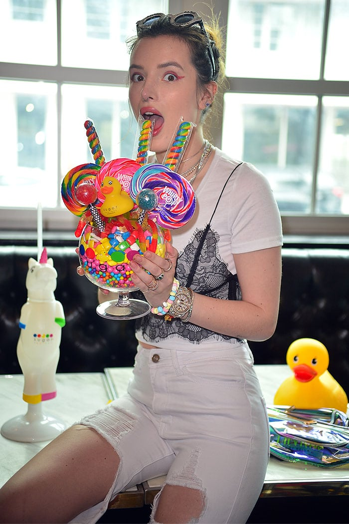Bella Thorne filling up on colorful candy stacked high in an oversized wine glass