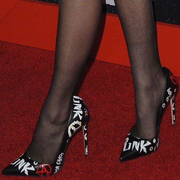 Closeup of Bella Thorne's punk print pumps and hairy legs in sheer black stockings