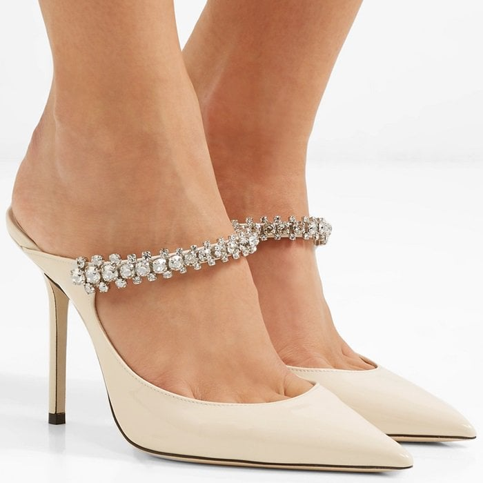 It's the sparkling crystal embellishments along the arch strap that lend an opulent touch to Jimmy Choo's cream patent leather Bing mules
