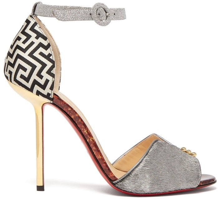 Christian Louboutin's silver Notte Bella 100 sandals are infused with an Art Deco aesthetic through their geometric-print suede detailing and walnut-finish vertiginous curve