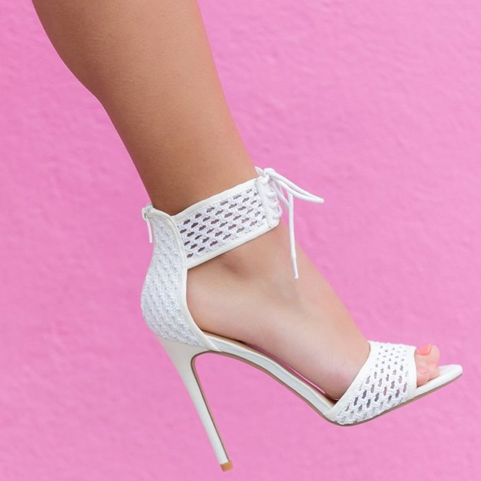 A stiletto-heeled sandal with a crochet lace-up detail and back zipper closure