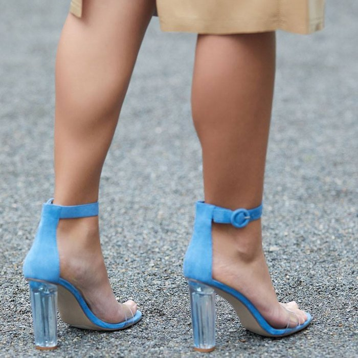 A two-piece sandal with a lucite block heel and ankle strap buckle closure.