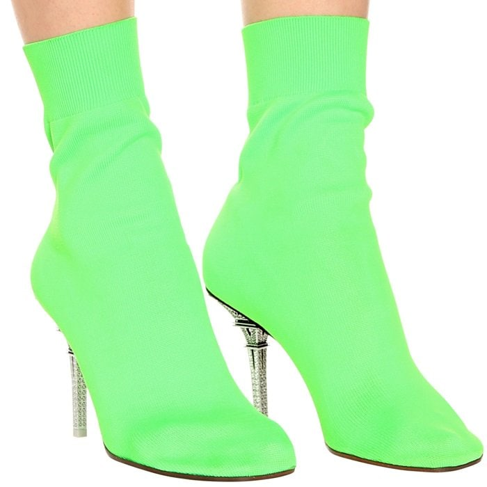 The pair has been crafted in Italy from neon green stretch knit and is perched high on a stiletto heel in the shape of the Eiffel Tower for a quirky touch.