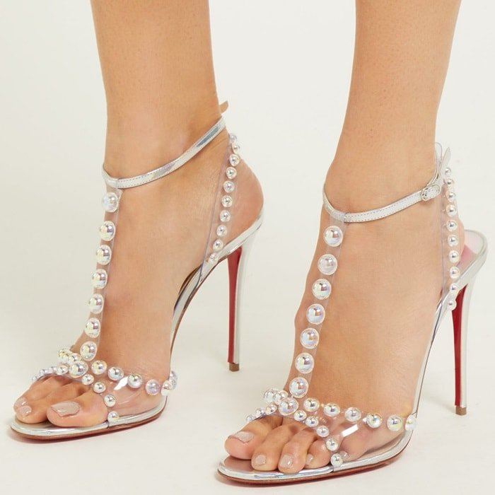 Iridescent bubble beads appear to float along the translucent straps of a striking sandal lifted by a skinny stiletto heel