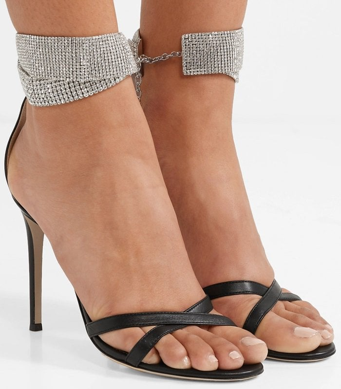 Crafted in Italy from smooth black leather, these sandals have shimmering crystal-encrusted ankle straps and are set on pin-thin heels
