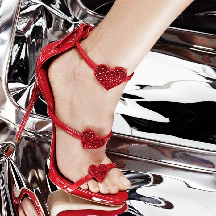 Crafted from poppy red patent leather, these sandals are set on a stiletto heel