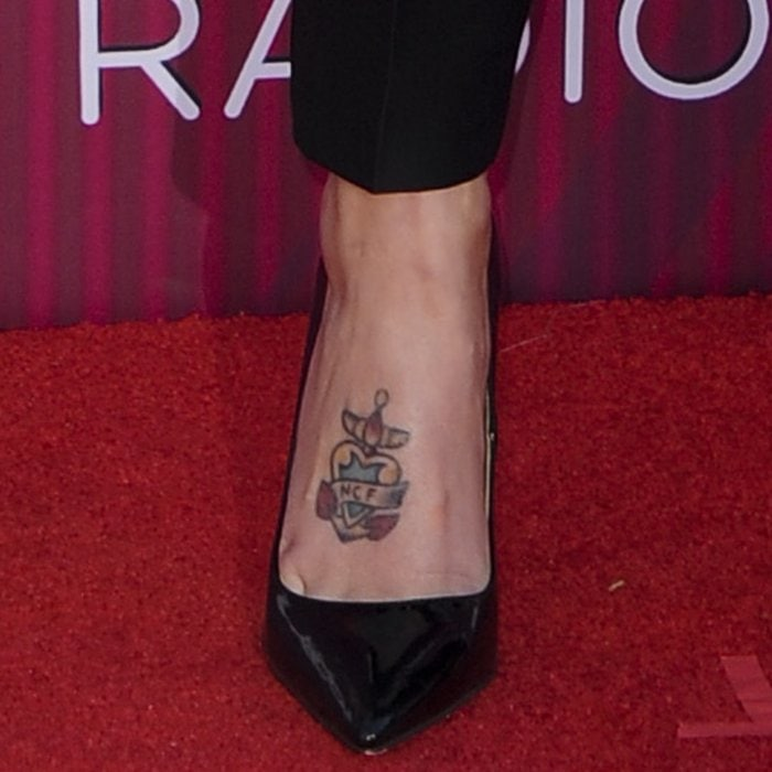 Halsey's anchor foot tattoo with a heart and a banner with her mother's initials NCF