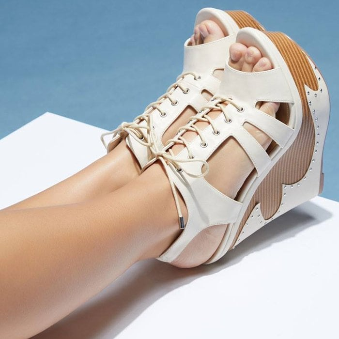 A studded platform wedge sandal with adjustable front laces.