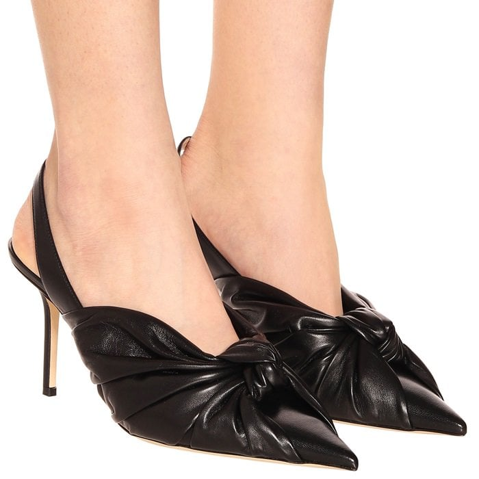 The pointed-toe silhouette features a ruched knotted front accent and is set on a stiletto heel