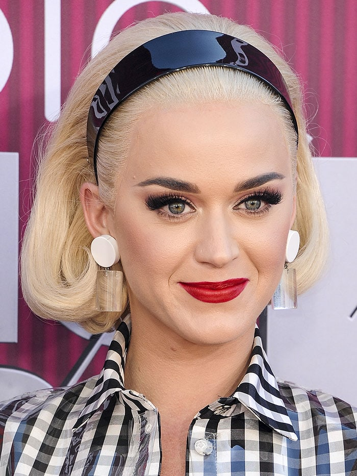 Katy Perry wearing a platinum-blonde lace-front wig, a shiny, black headband, and vintage circle lucite earrings