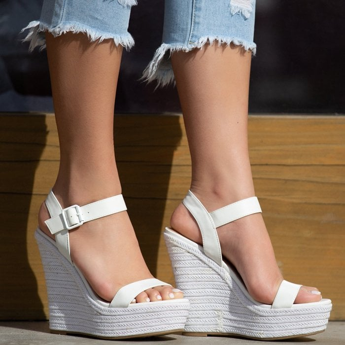 A two-piece platform espadrille wedge sandal with an adjustable ankle buckle strap closure.