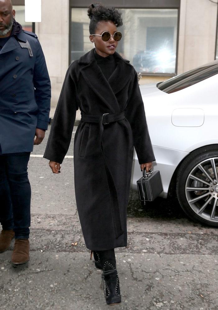 Lupita Nyongo wearing a Max Mara coat and an Ara Vartanian ring after visiting BBC Radio 2 in London, United Kingdom, on March 15, 2019