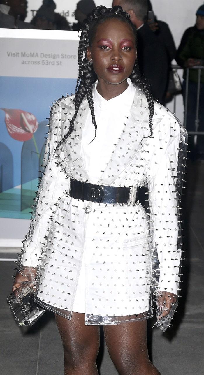 Lupita Nyong'o in a white button-down shirt dress