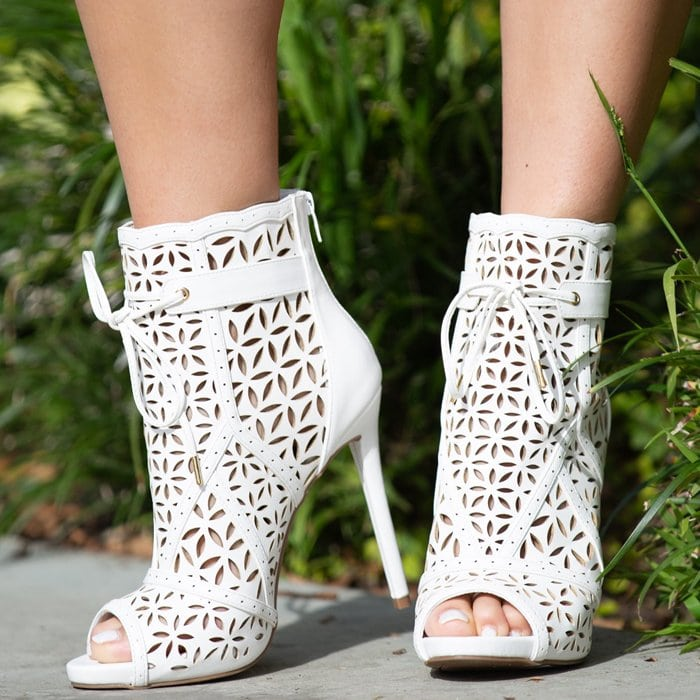A pointed-toe laser cut bootie with a gold toe detail and side zipper closure.