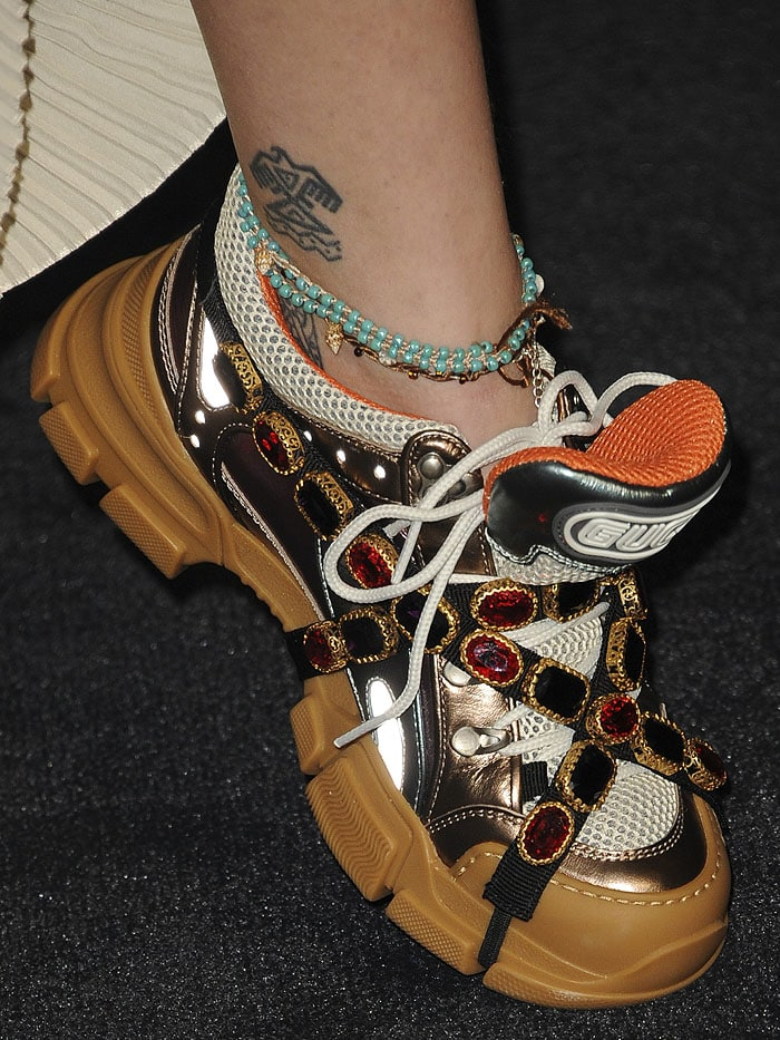 Closeup of Paris Jackson's Gucci ''Flashtrek' crystal-wrapped sneakers and tribal eagle ankle tattoo