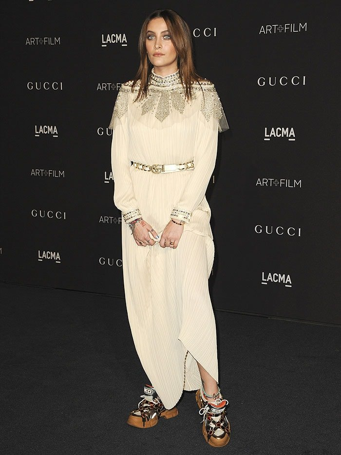 Paris Jackson wearing a Gucci Spring 2018 embellished-capelet pleated gown with a Gucci belt and Gucci sneakers