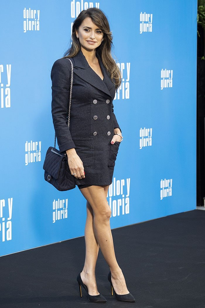 Penelope Cruz in a Chanel Resort 2019 double-breasted coat dress and classic black-satin pumps