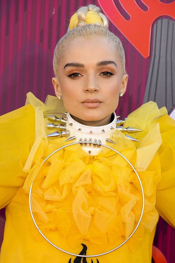 Poppy accessorizing with a spiked white choker featuring a massive ring pendant