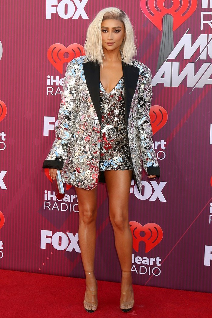 Shay Mitchell in a Nicolas Jebran 2019 mirror-cutout jacket and dress, AS29 earrings, Julien Macdonald triple-strap clear sandals, and carrying a Tyler Ellis clutch