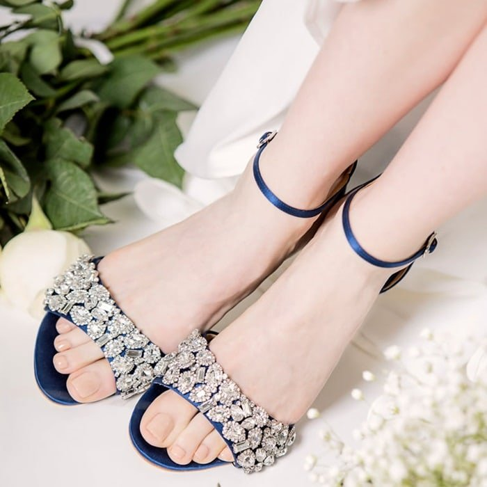 A kitten heel open toe sandal with jewelry inspired crystal ornamentation across the toe and a delicate ankle strap with buckle closure