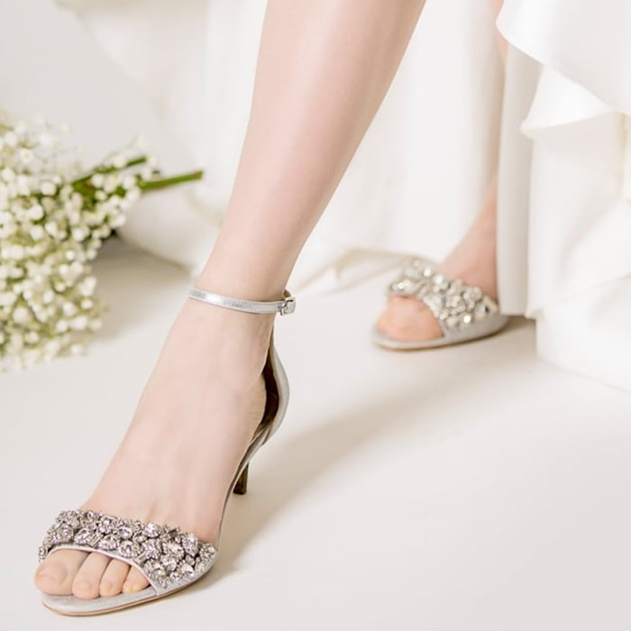 Dazzling crystals sparkle across the toe strap of a kitten-heel sandal secured by a slender ankle strap