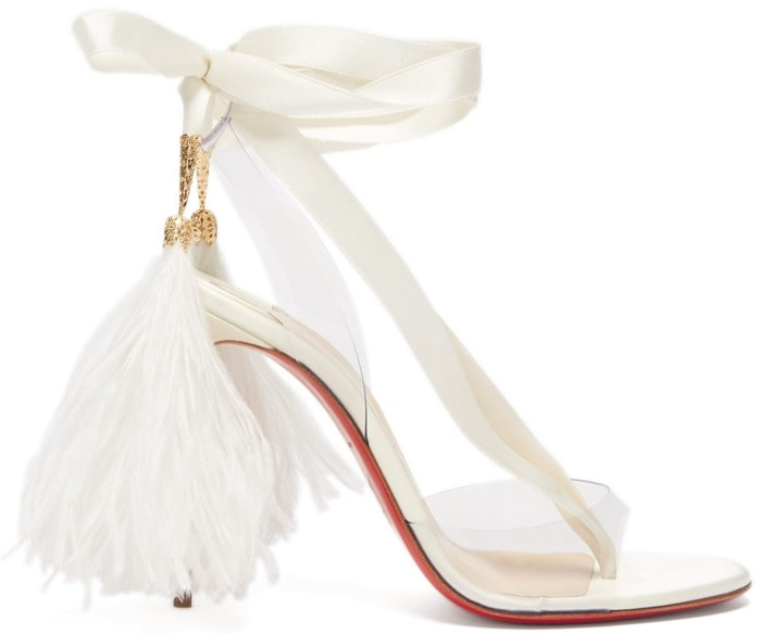 Crafted in off-white crepe satin and sitting atop a slender 100mm stiletto heel, it uses a toe strap and counter in clear PVC to float a tonal grosgrain ribbon that starts at the vamp, wraps around and elegantly hugs the ankle several times before ending with real ostrich feathers held by a guilloche engraved metal bell and hand-dyed by Lergeron