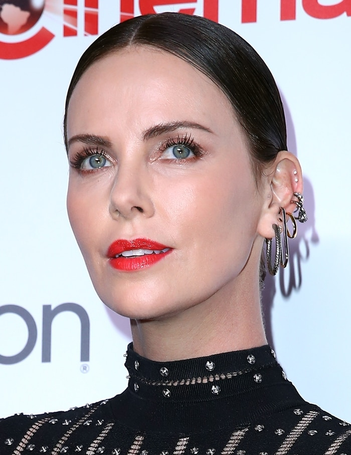 Charlize Theron with her brown hair slicked back to show of her Alexander McQueen earrings