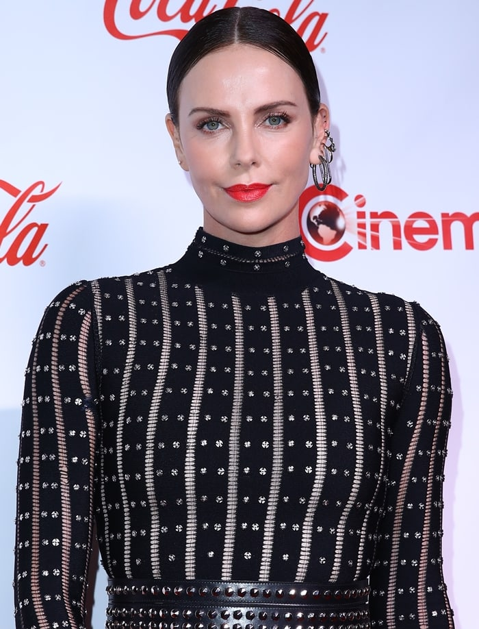 Charlize Theron's belted spike long sleeve lattice cutout dress inspired by machinery and metalwork