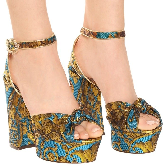 The statement-making silhouette has been crafted in Italy with an ornate blue and golden upper, golden leather trim and a crystal-embellished buckle for a shimmering finish