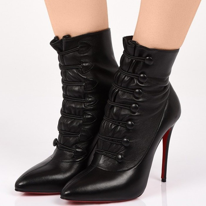 The black nappa leather high-upper is delicately set on a stiletto heel of 100mm and adjusts with the help of lacing that fits into lateral button rows