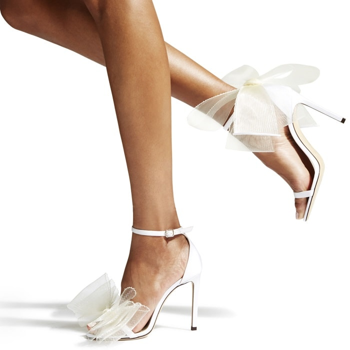 An oversized bow finish adds whimsy to these thin ankle-strap pumps