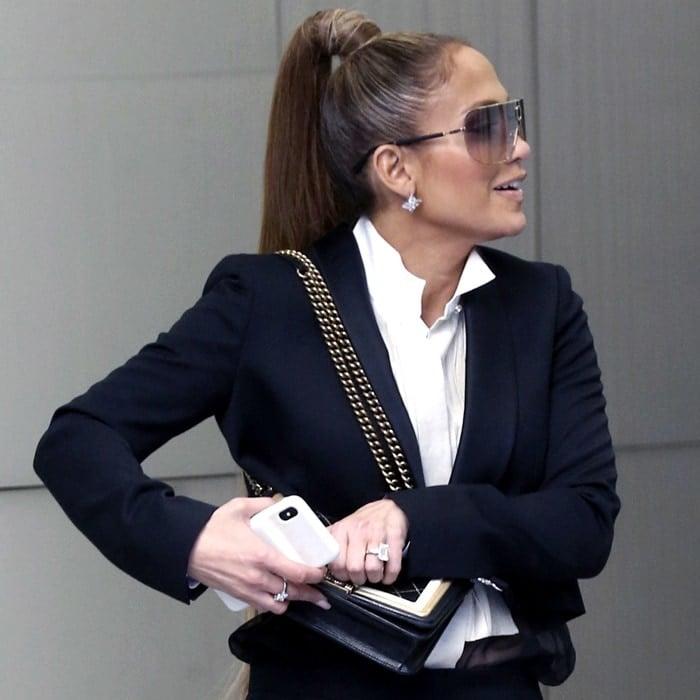 Jennifer Lopez wearing an Ariana Grande ponytail and a Chanel 'Chateau Boy' bag