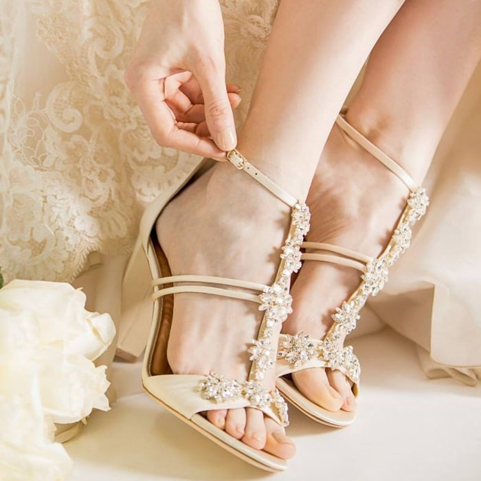Step out in glamorous ivory style with this block-heel sandal featuring sparkling crystals along the T-straps