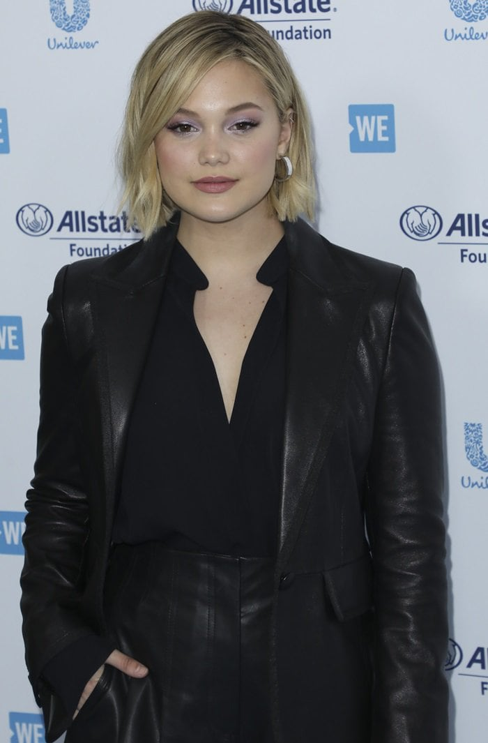 Olivia Holt's supple black leather Paulie blazer is cut for a slim fit and has tactile grosgrain trims outlining the sharp peak lapels and flap pockets