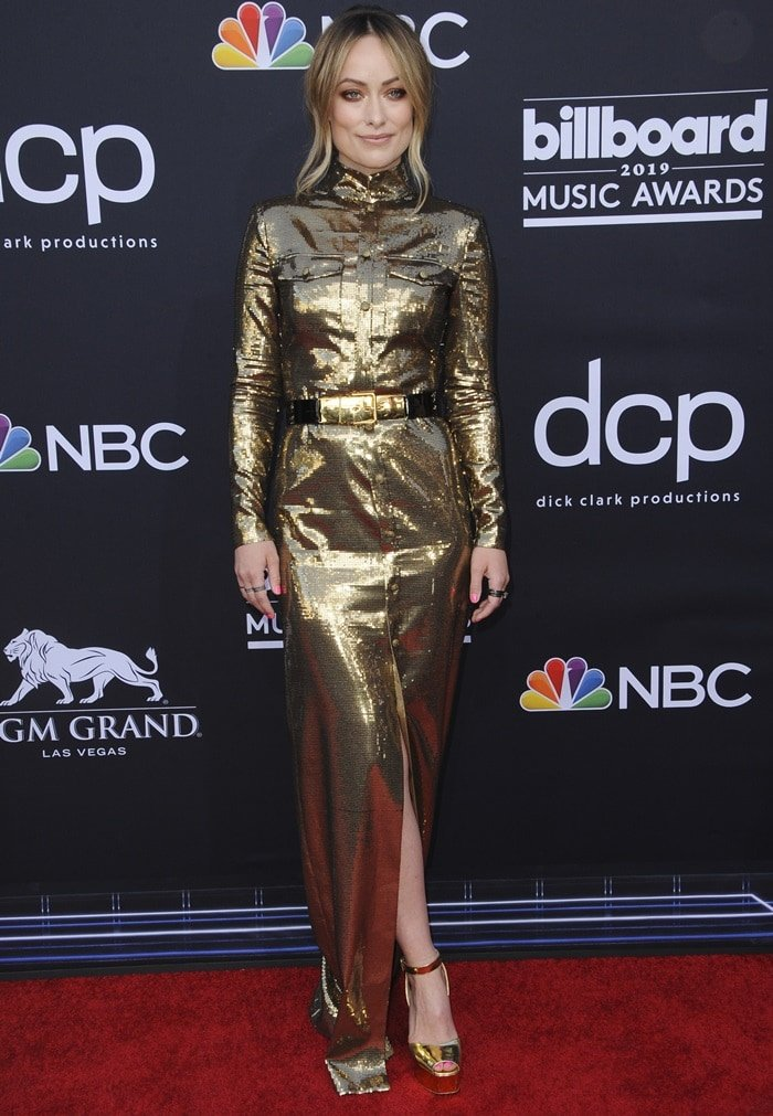 Olivia Wilde in a long sleeve gold sequin dress at the 2019 Billboard Music Awards