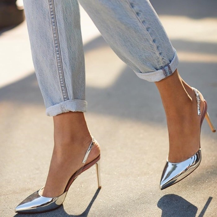 Of-the-moment translucent insets at the slingback strap distinguish a high-shine pump in a pointy-toe silhouette
