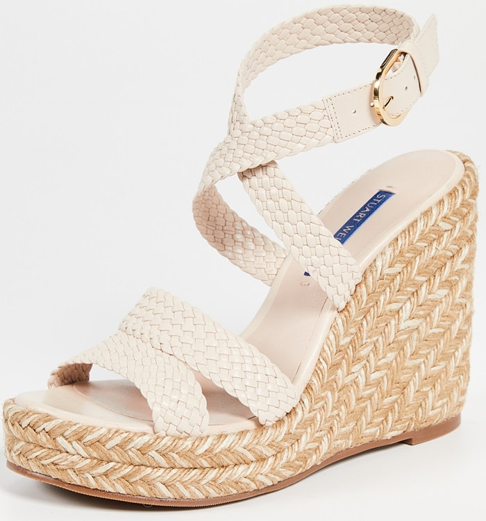 A platform wedge wrapped in braided, tri-color jute boosts the textural richness of a sandal featuring beautifully woven straps