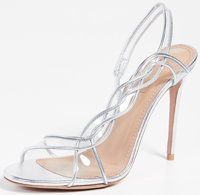 Crafted from metallic leather in shimmery silver, this sandal features intricate straps with on-trend PVC that cascade up the foot and wrap around the ankle