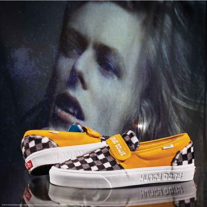 This slip-on style combines the iconic low profile silhouette with sturdy textile and suede uppers, a hook-and-loop closure, the signature Vans checkerboard print, and custom Bowie details