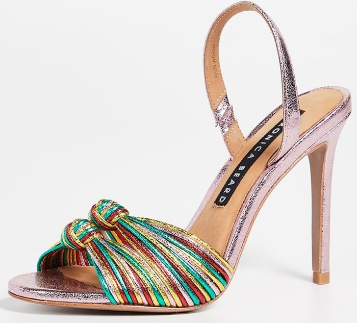 Slim metallic straps are gathered and knotted together at the toe of a dazzling evening sandal set on a tall stiletto