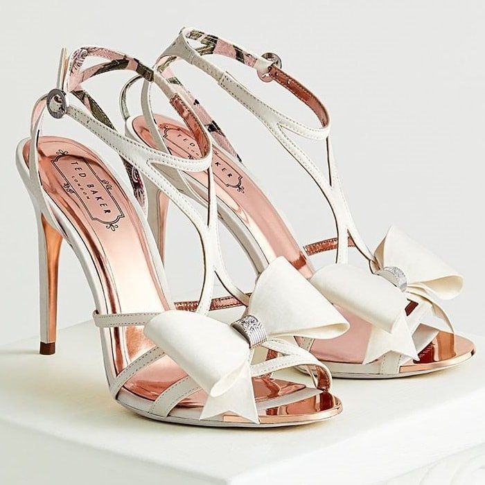 A signature bow punctuates this lofty stiletto sandal with timeless sophistication