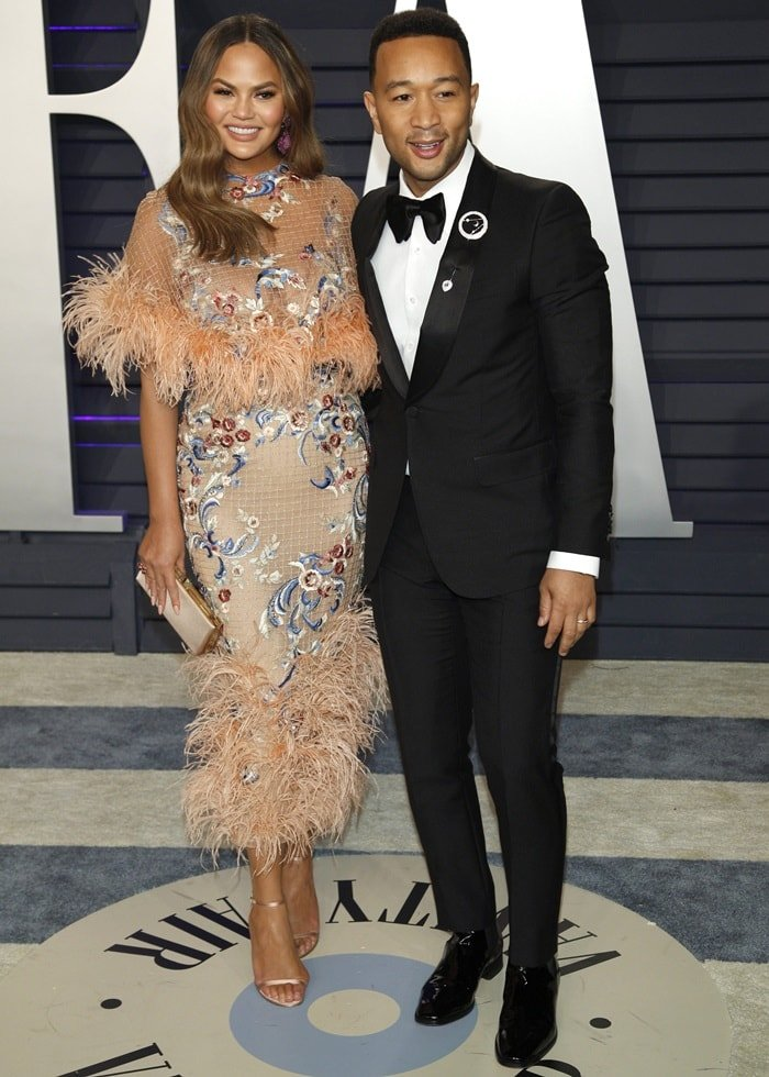 Chrissy Teigen and her husband John Legend pose together as they arrive at the 2019 Vanity Fair Oscar Party