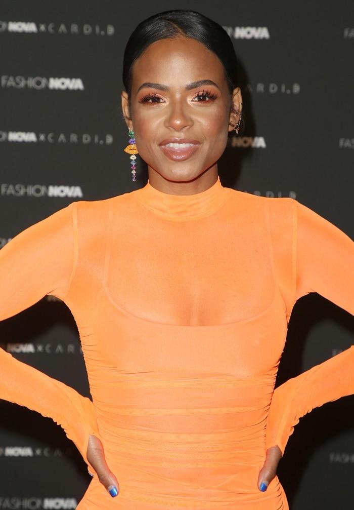 Christina Milian's neon orange ruched midi dress
